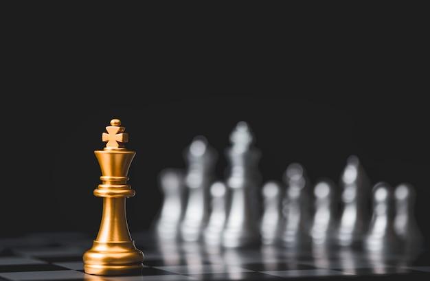 Złote szachy królewskie stoją samotnie wśród srebrnych szachowych wrogów po przeciwnej stronie