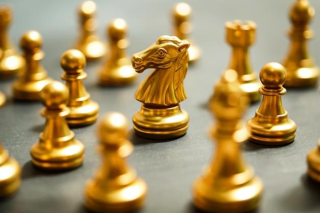 Złote szachy na czarnym tle, koncentrują się na rycerzu