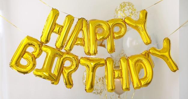 Złote szczęśliwe urodziny słowa wykonane z balonów