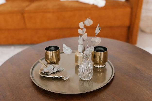 Złote szklanki, suszone kwiaty w wazonie na okrągłej tacy na stoliku kawowym