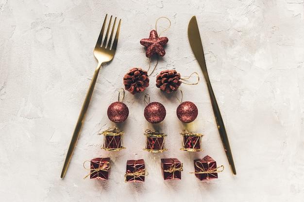 Złote sztućce na świątecznej dekoracji na białej powierzchni