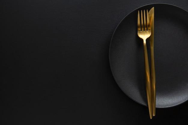Złote sztućce z tekstyliami na talerzu na ciemnym tle. widok z góry.