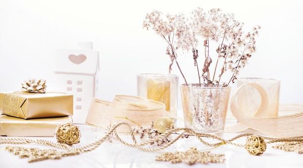 Złote tło boże narodzenie, spa lub koncepcja piękna. złote świece, prezenty, wstążki, suche puszyste rośliny