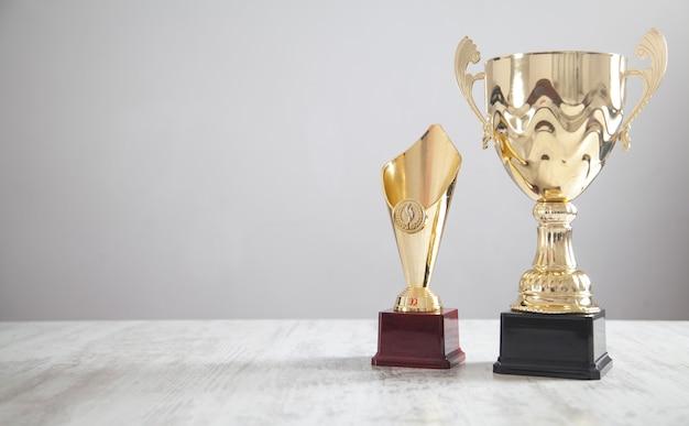 Złote trofeum na białym biurku. sukces biznesowy