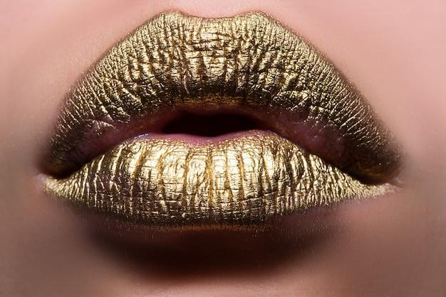 Złote usta. kobieta wouth bliska złotym kolorem szminki na wardze. błyszczące, błyszczące usta przygryzające.