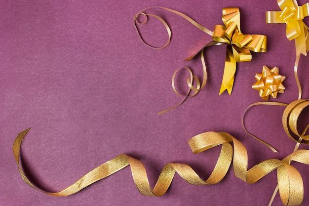 Złote wstążki na fioletowym tle