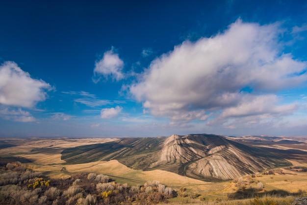 Złote wzgórza, małe góry na tle błękitnego nieba z chmurami