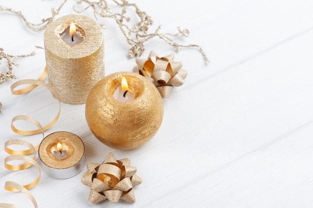 Złote zapalone świece zapachowe i świąteczne zabawki na drewnianym tle rustykalnym
