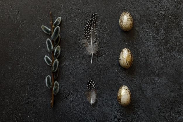 Złote zdobione pisanki z piór wierzby na modny grunge porysowany ciemny czarny łupek
