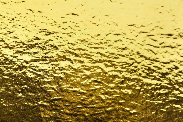Złotej folii liścia opakowania papieru tekstury błyszczący tło dla ściennego papieru dekoraci elementu