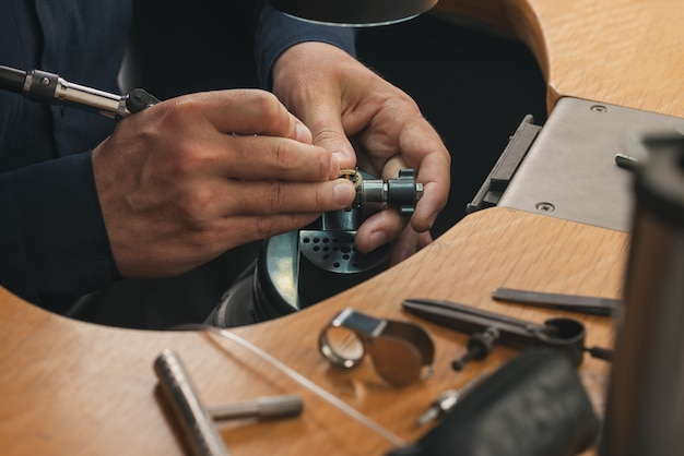 Złotnik w pracy. stół jubilerski z różnymi narzędziami. pulpit do tworzenia biżuterii rzemieślniczej za pomocą profesjonalnych narzędzi.