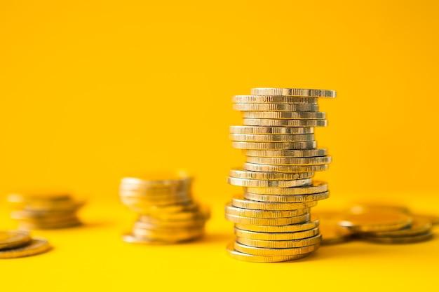 Złoto żółte światło z stosu monet na żółtym bakground.