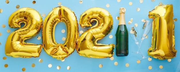 Złoty balon 2021 z butelką i kieliszkami do szampana z konfetti. szczęśliwego nowego roku
