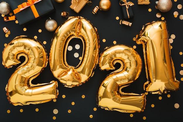 Złoty balon 2021 z konfetti, pudełka na prezenty, złote kule, świąteczny wystrój szczęśliwego nowego roku 2021.