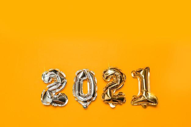 Złoty balon foliowy 2021 lecący w powietrzu na żółtym tle.