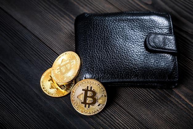 Złoty bitcoin i czarna kiesa na drewnianym tle