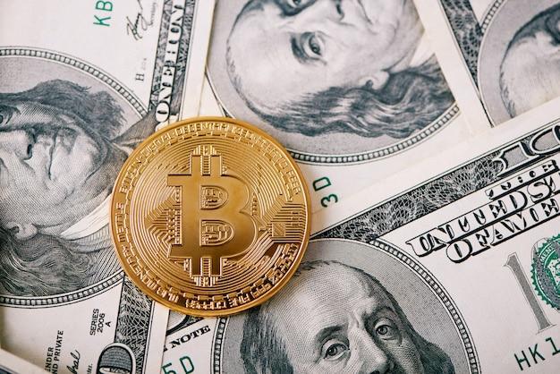 Złoty bitcoin jako najważniejsza kryptowaluta na świecie ze sto banknotów dolarowych na tle