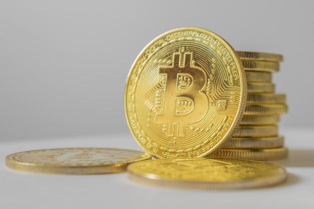 Złoty bitcoin na białym stole i tle - koncepcja biznesowa kryptowaluty.