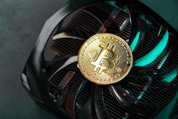 Złoty bitcoin na chłodnicy karty graficznej na ciemnej powierzchni widok z góry