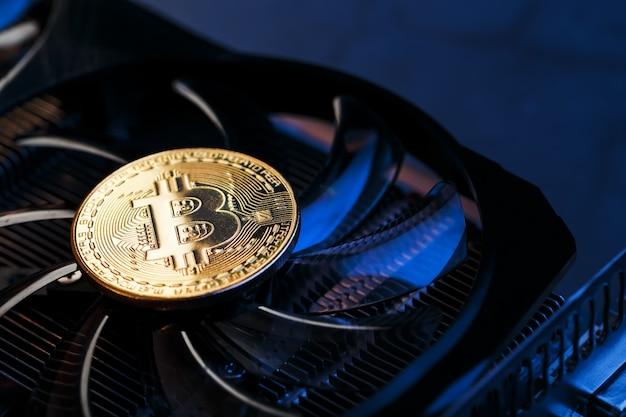 Złoty bitcoin na chłodnicy karty graficznej na ciemnym tle widok z góry