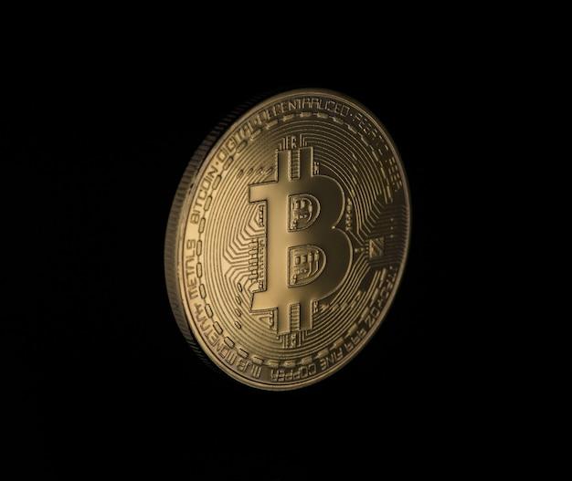 Złoty bitcoin na czarnym tle, zbliżenie. pieniądze elektroniczne na białym tle