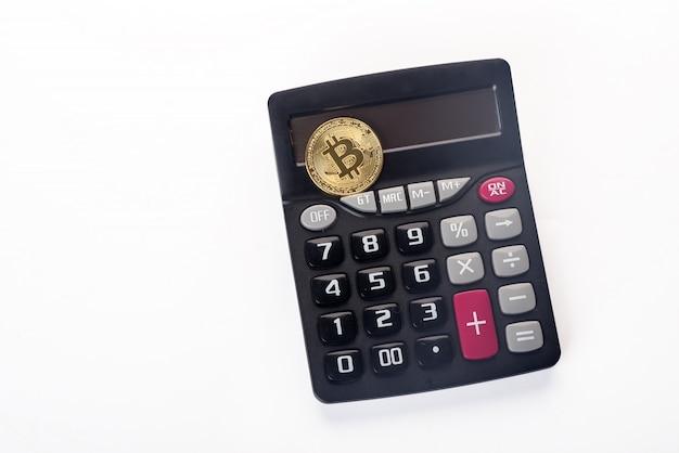 Złoty bitcoin na defocused kalkulatorze
