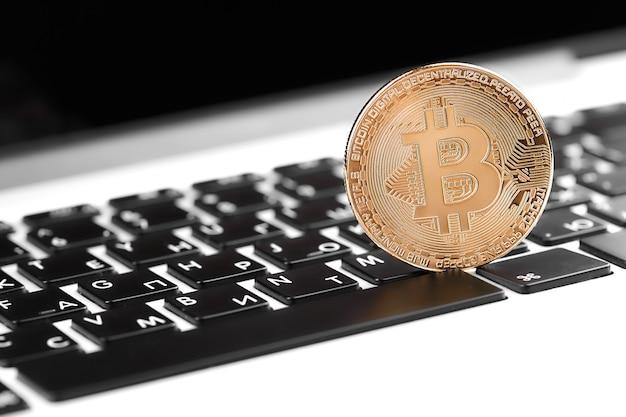 Złoty bitcoin na komputerowej klawiaturze, zbliżenie. bitcoiny i wirtualne pieniądze