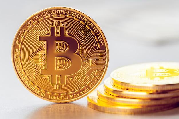 Złoty bitcoin na tle sterty innych bitcoinów