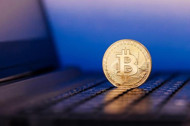 Złoty bitcoin stoi nad klawiaturą