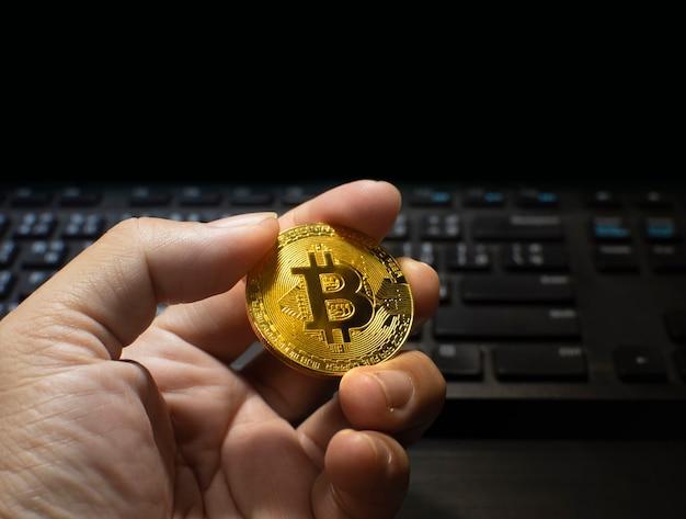 Złoty bitcoin trzymający w dłoni z klawiaturą komputera rozmazaną na tle i górną czarną przestrzenią do kopiowania, wirtualne pieniądze kryptowaluty i koncepcja technologii blockchain
