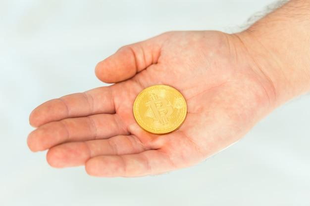 Złoty bitcoin w dłoni mężczyzny