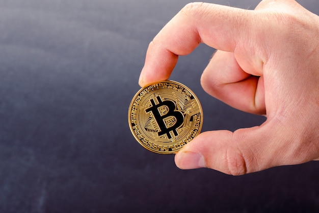 Złoty bitcoin w ręce mężczyzny