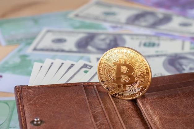 Złoty bitcoin z dolarami w brązowym skórzanym portfelu