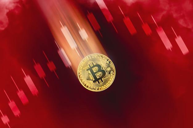 Złoty bitcoin zmniejszający wartość i spadek ceny, wykres wykresu świecowego trendu spadkowego i czerwony kolor tła z dymem, koncepcja wirtualnego pieniądza kryptowaluty