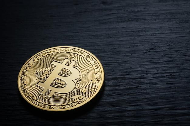 Złoty błyszczący bitcoin na czarnej drewnianej ścianie