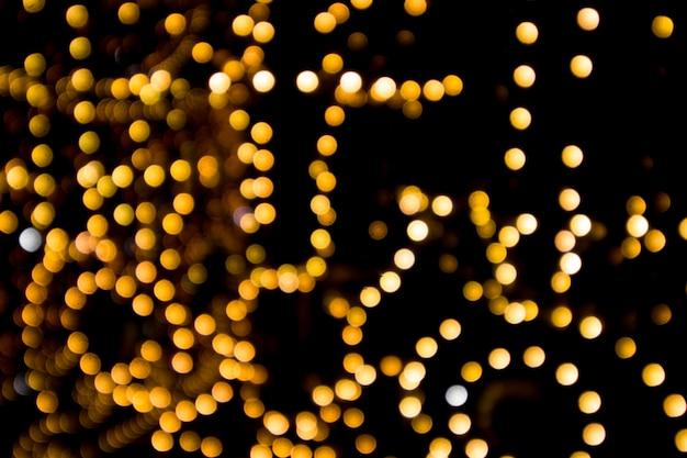 Złoty bokeh na czarnym, niewyraźne światło girlandy