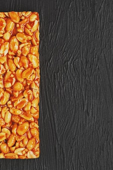 Złoty borowik kozinaki z batonów energetycznych z prażonej fasoli orzechowej. czarne tło teksturalne, widok z góry