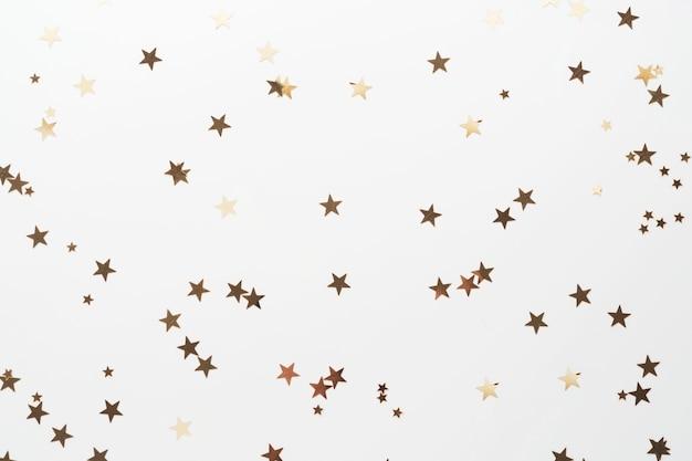 Złoty brokat, gwiazdy konfetti na białym tle. boże narodzenie, przyjęcie lub tło urodzin.
