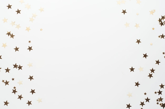 Złoty brokat, gwiazdy konfetti na białym tle. boże narodzenie, przyjęcie lub urodziny tło.