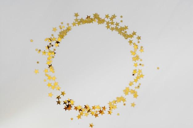 Złoty brokat rama koło, gwiazdy konfetti na białym tle. boże narodzenie, przyjęcie lub urodziny tło.