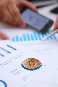 Złoty btc znaka monety lying on the beach przy statystyki wykresu zbliżeniem.