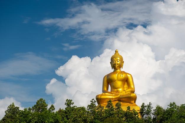 Złoty budda i białe chmury. posąg buddy z dużymi chmurami z miejsca na kopię.