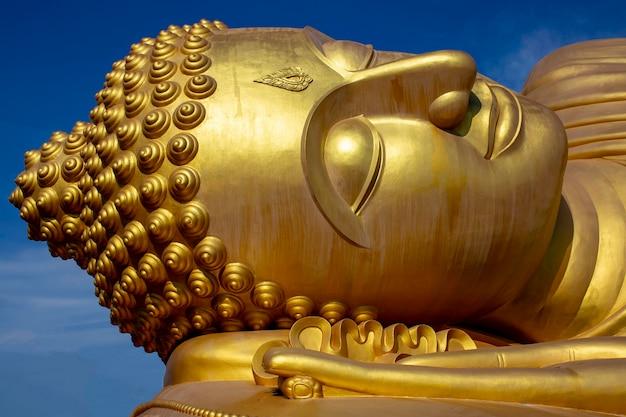 Złoty budda leżący budda posąg pana w buddyjskiej świątyni w tajlandii błękitne niebo
