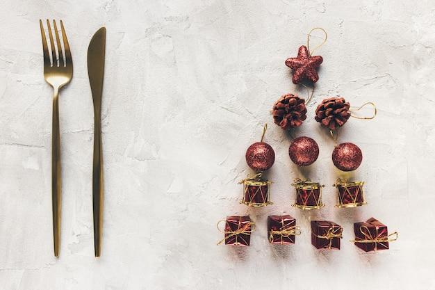 Złoty cutleru i czerwona dekoracja na szarym tle. ferie zimowe gotowanie uroczystej kolacji, menu świąteczne i noworoczne oraz koncepcja uroczystości. widok z góry, płaski układ, miejsce na kopię