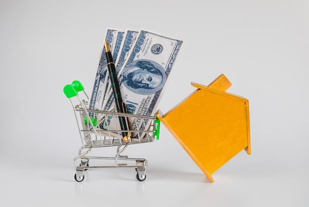Złoty dom z wózkiem na zakupy, koncepcja mieszkania i nieruchomości.