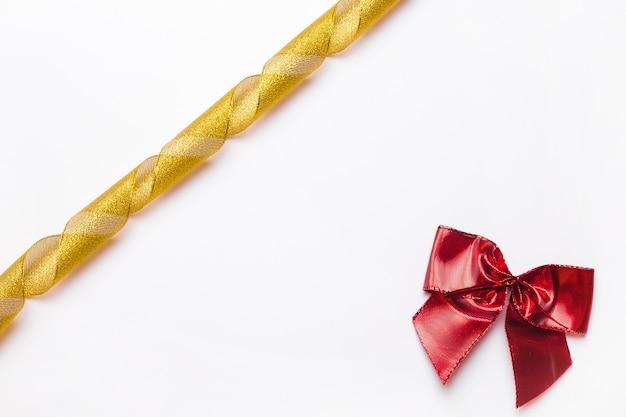 Złoty faborek i czerwony łęk na białym tle