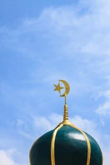 Złoty islamski symbol religijny na szczycie kopuły meczetu