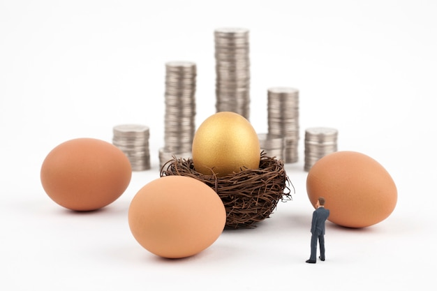 Złoty jajko i biznesowy mężczyzna na bielu