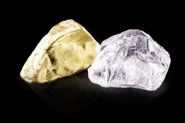 Złoty kamień i surowy diament na na białym tle czarnym tle, koncepcja rzadkich i cennych minerałów.