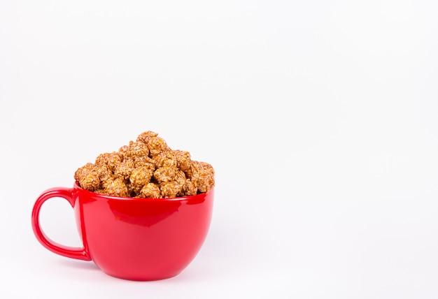 Złoty karmelizujący popkorn w czerwonym pucharze na białym tle